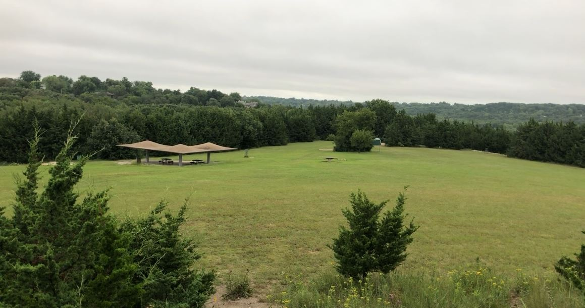 the view of Warner Park from tee 9, trees, meadow, and park shelter