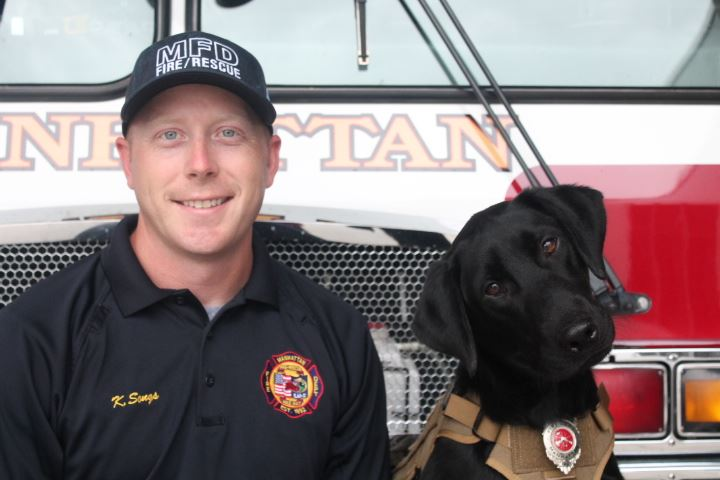 photo of Duke the fire dog and Kody Songs posing in front of a fire truck
