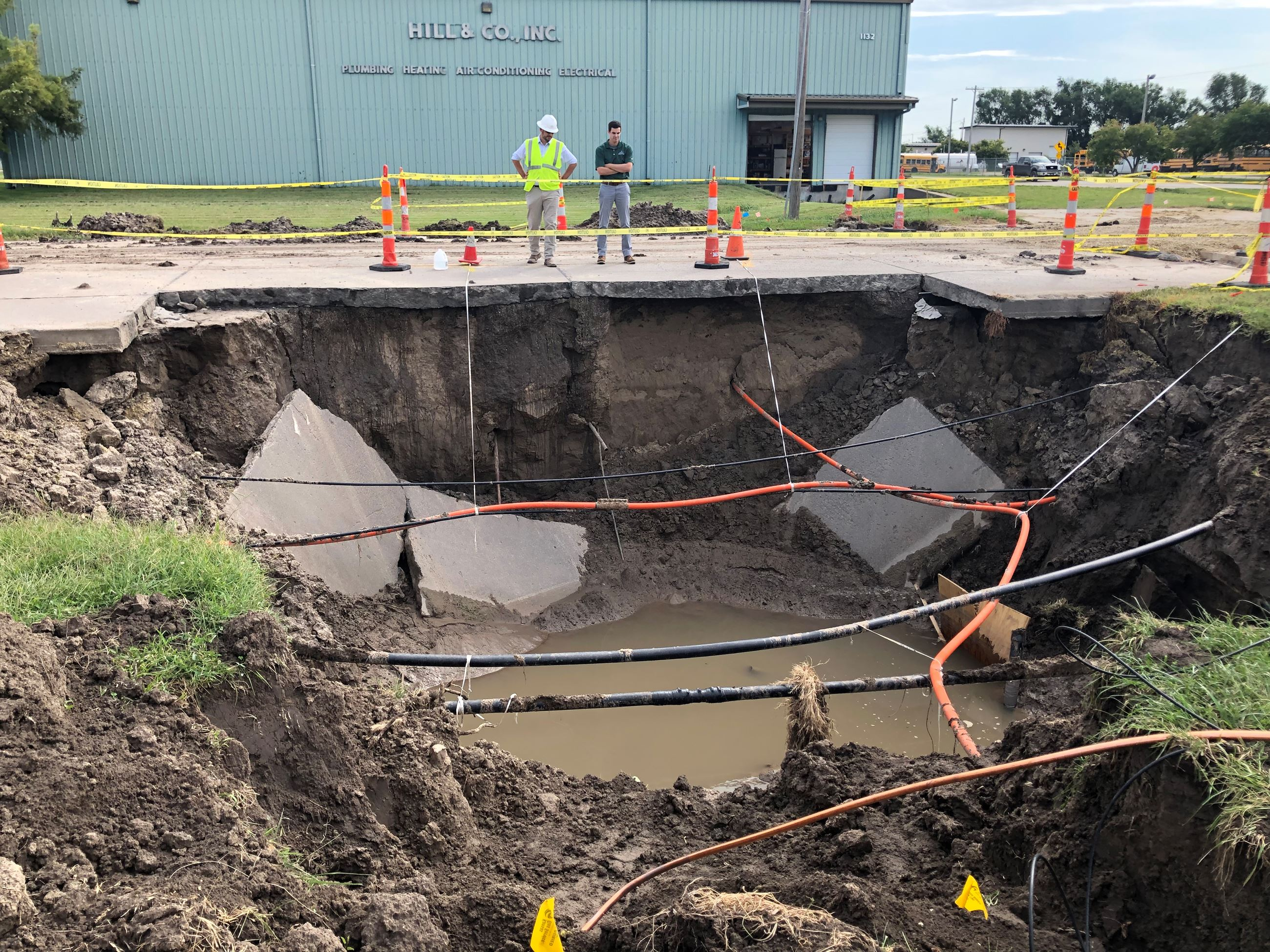 photo of two men standing near the Hayes Drive sinkhole
