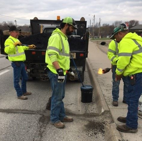 crew of four men patching potholes